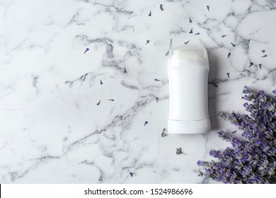 Female deodorant and lavender flowers on white marble background, flat lay. Space for text
