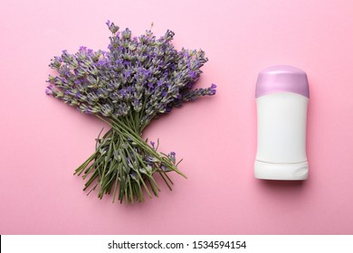 Female deodorant and lavender flowers on pink background, flat lay