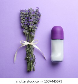 Female deodorant and lavender flowers on lilac background, flat lay