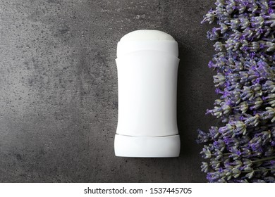 Female deodorant and lavender flowers on grey stone background, flat lay