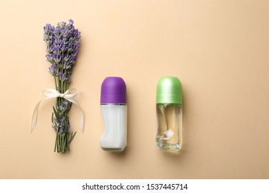 Female deodorants and lavender flowers on beige background, flat lay