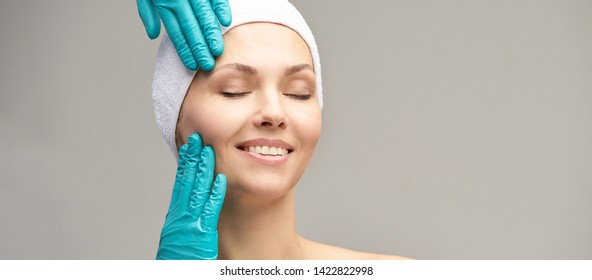 Female derma rejuvenate treatment. Doctor in gloves touch woman face. Cosmetology pretty portrait. Facial injection patient.