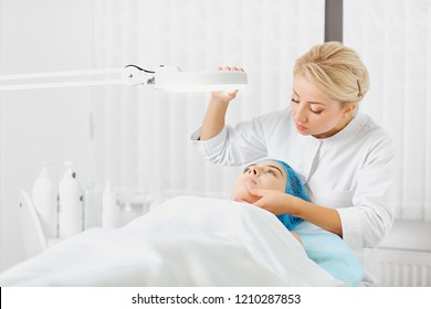 A female dermatologist examines the face of a girl.