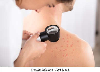 Female Dermatologist Examining Acnes Of Patient With Dermatoscope