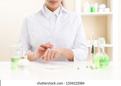 Female dermatologist testing skin care product at table, closeup
