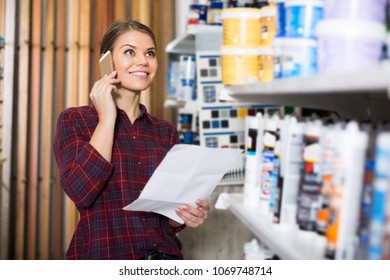 Female designer is choosing paint with list for redecorate house and talking by phone in the store