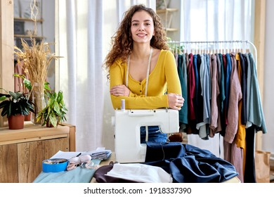 female designer of clothes standing by sewing machine in atelier, attractive tailor after work stand posing, looking at camera smiling. female use measuring tape for sewing and making garments - Shutterstock ID 1918337390