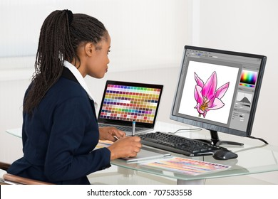 Female designer drawing flower on computer using graphic tablet at desk in office