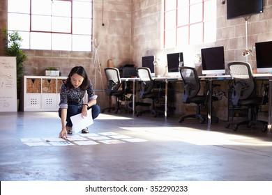 Female Designer Planning Layout On Floor Of Modern Office