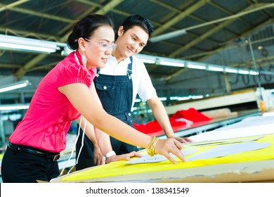 Female Designer or a seamstress and worker or production manager look at pattern on a table in a textile factory