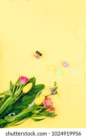 Female desk workspace with cosmetics, lipstick and tulip flowers on yellow background. Spring flowers, spring concept.
