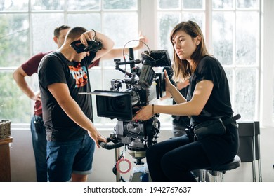 Female director of photography with a camera on a movie set. Professional videographer on the set of a movie, commercial or TV series. Filming indoors, studio
