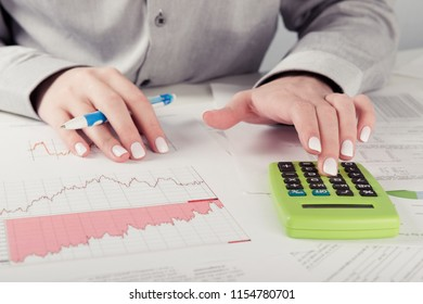 Female director working in office sitting at desk analyzing business statistics holding diagrams and charts