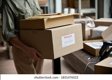 Female distribution warehouse worker or seller holding ecommerce shipping order boxes preparing for dispatching, post courier delivery dropshipping commerce retail shipment service concept, closeup.