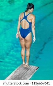 Female diver standing on the jumping board. Preparing to jump into the pool