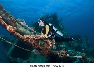 Female diver swimming over a shipwreck in the Southern Red Sea, Egypt