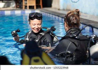 Female diving instructor teaches student to scuba dive in swimming pool. Lady getting first experience with scuba diving under the guidance of experienced recreational diving instructor on vacation.