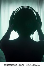 Female DJ deejay woman wearing closed headphones listening to music in artistic photo.