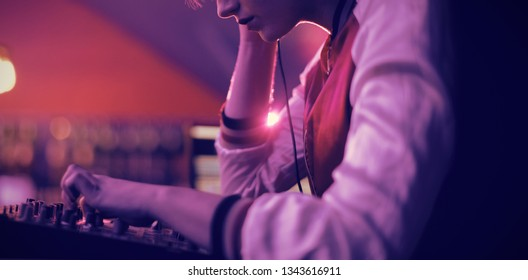 Female dj listening to headphones while playing music in bar