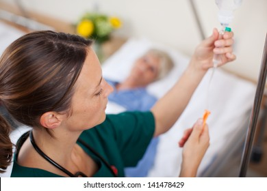 Female doctor adjusting infusion bottle with patient lying on bed in hospital