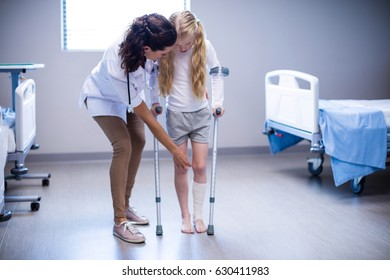 Female doctor assisting girl to walk with crutches in ward of hospital