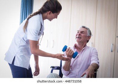 Female doctor assisting senior man in lifting dumbbell at home