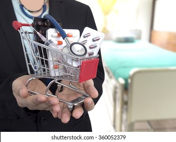 Female Doctor with black suit with hospital bed blur background. She's holding small shopping cart with colorful pills, syringe and stethoscope. Concept for health care costs or medical insurance.