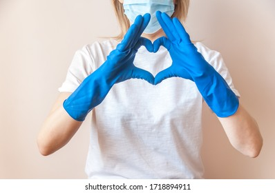 A female doctor in blue medical gloves, white T-shirt and blue medical mask on face makes a heart out of her hands. Thanks to health workers concept. Gratitude to the medical staff.