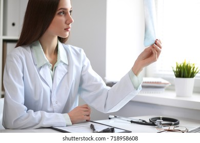 Female doctor brunette looking at x-ray  while sitting  at the table near the window in hospital. Physician is ready to help patient. Medicine and health care concept