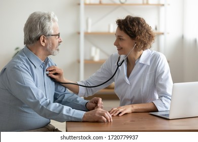 Female doctor cardiologist examining senior male cardiac patient listening checking heartbeat using stethoscope at checkup hospital visit. Old people medicare, elderly healthcare cardiology concept.