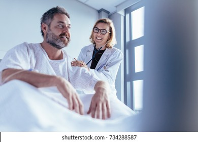 Female doctor checking male patient. Doctor visiting and talking with patient sitting in a hospital bed.