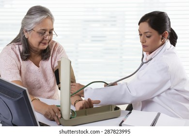 Female doctor checking patient's blood pressure