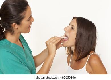 Female doctor checking for sore throat