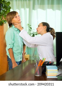 Female doctor checking thyroid of teenager boy in clinic office