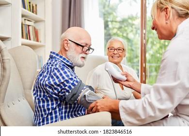 Female doctor checks the blood pressure of a senior citizen in his senior citizen apartment