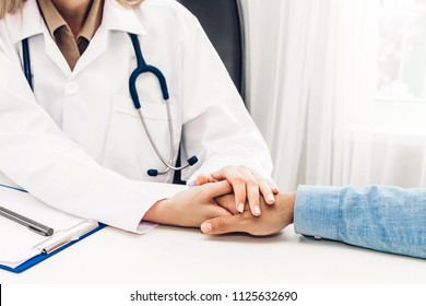 Female doctor consulting and holding hand male patient reassuring with care on doctors table in hospital.healthcare and medicine