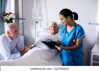 Female doctor discussing with senior couple over a report in the ward at hospital
