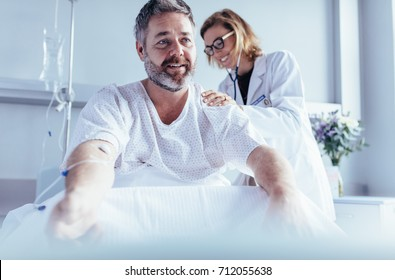 Female doctor examine patient's back. Mature man sitting in hospital bed and physician doing checkup.
