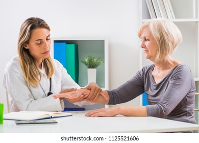 Female doctor examines her senior patient's wrist in office.