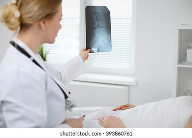Female Doctor examines an X-ray picture of the spine next to  patient lying in the bed  in hospital