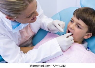 Female doctor examing boy mouth at dental clinic