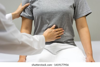 Female doctor are examining by abdominal palpation of female patient sitting in the bed within the clinic.