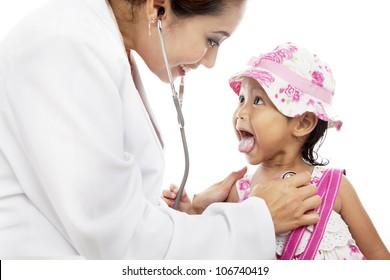 Female doctor examining cute little girl using stethoscope