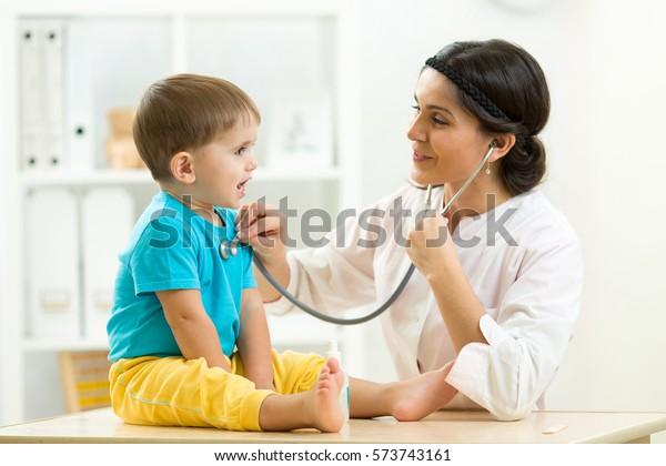 Female Doctor Examining Little Child Boy Stock Image