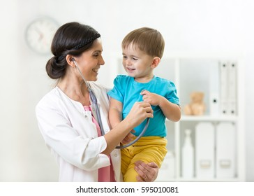 Female doctor examining little boy with stethoscope