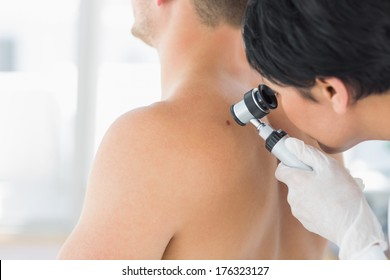 Female doctor examining mole on back of man in clinic