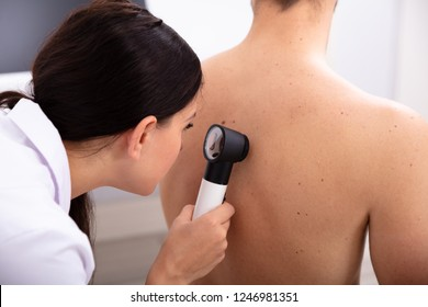 Female Doctor Examining Pigmented Skin On Man's Back With Dermatoscope