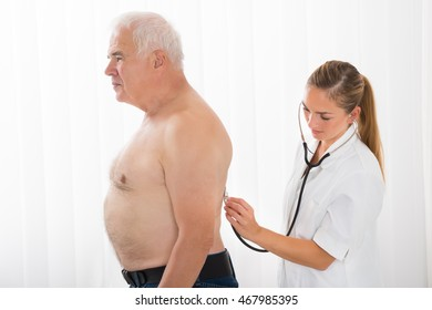 Female Doctor Examining Senior Male Patient With Stethoscope In Hospital