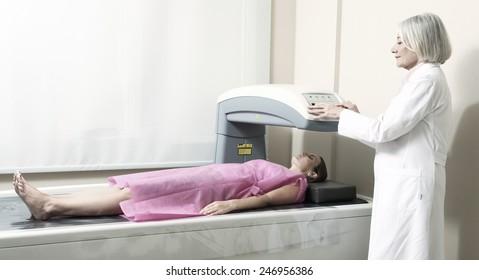 Female doctor examining woman in 40s at Bone Densitometer Machine.