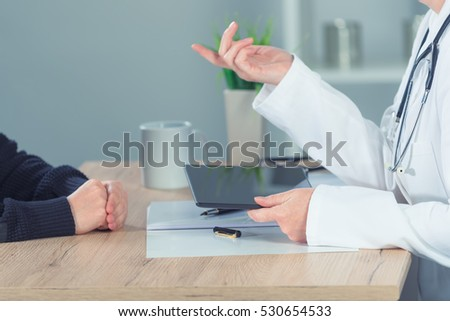 Female doctor explaining situation to patient in hospital office during regular medical exam, healthcare and prevention concept